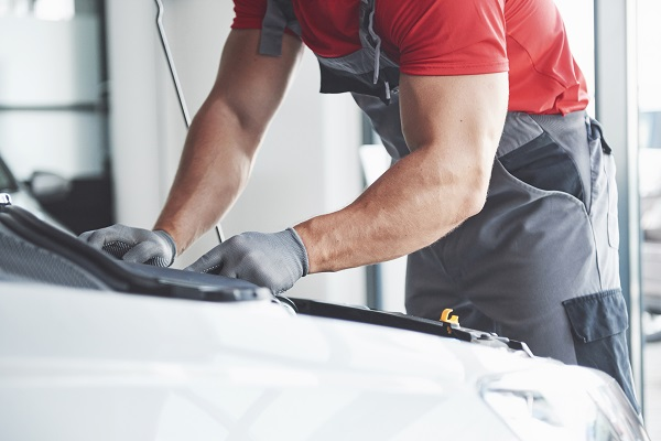 Picture showing muscular car service worker repairing vehicle